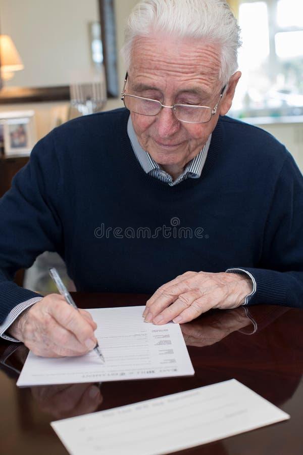 Älterer Mann-unterzeichnendes Testament zu Hause lizenzfreies stockfoto