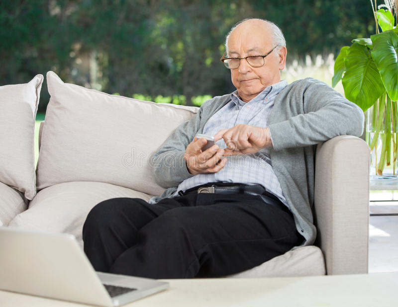 Älterer Mann-Versenden von SMS-Nachrichten durch Smartphone an stockfotografie