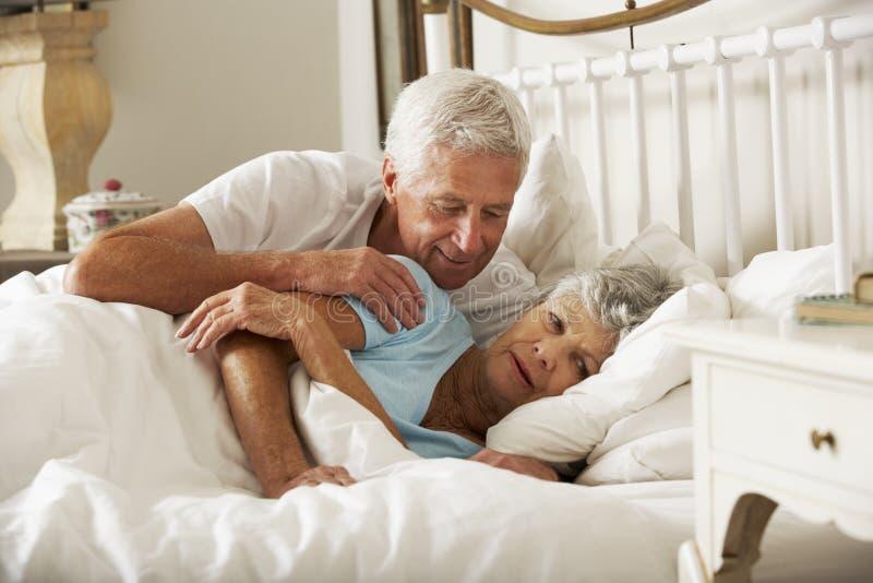 Älterer Mann-Versuche, zum in Richtung zur Frau im Bett liebevoll zu sein stockfoto