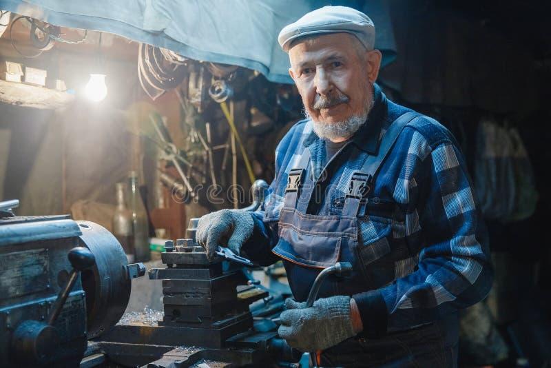 Älterer älterer Mannes-Turner-Mechaniker, der an Werkzeugmaschine für Metall arbeitet stockfotos
