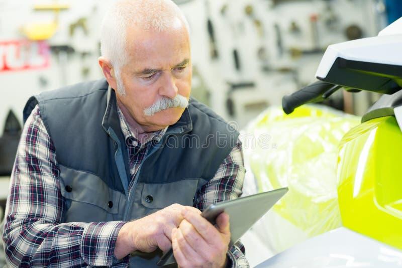 Älterer Mechaniker, der digitale Tablette verwendet lizenzfreie stockbilder