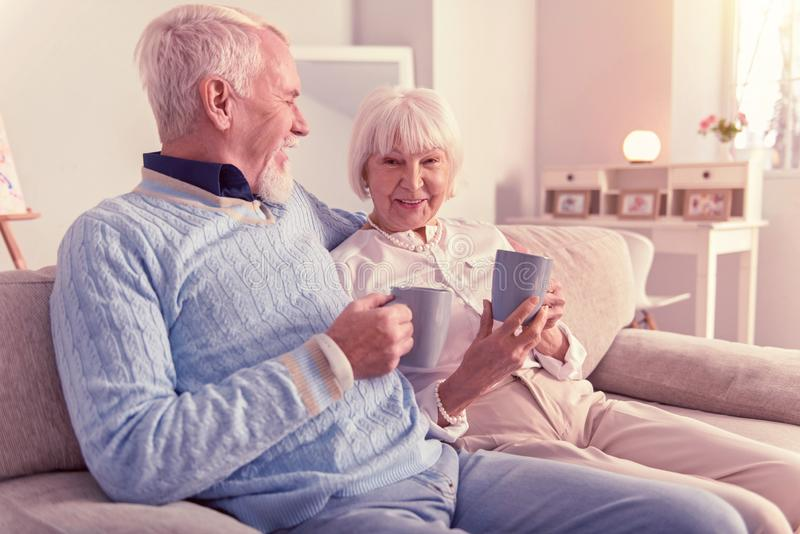 Älterer netter Mann, der seine lächelnde Frau umarmt stockfotografie