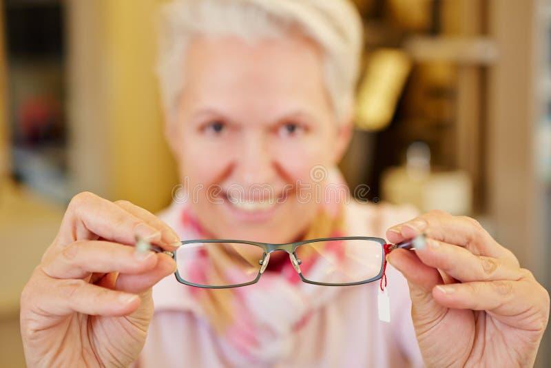 Älterer Optiker, der Gläser hält stockfotos