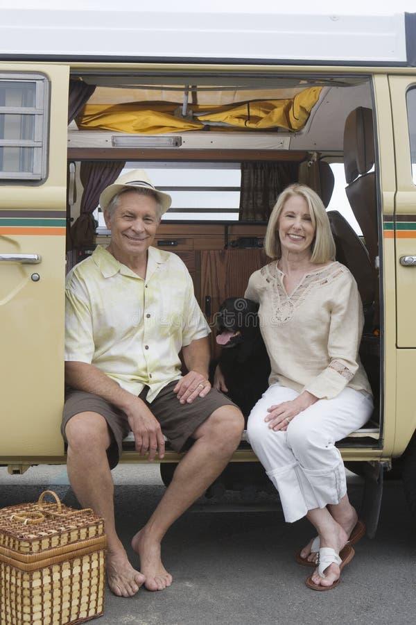 Älterer Paar-Sit In Campervan With Their-Schoßhund lizenzfreie stockfotografie