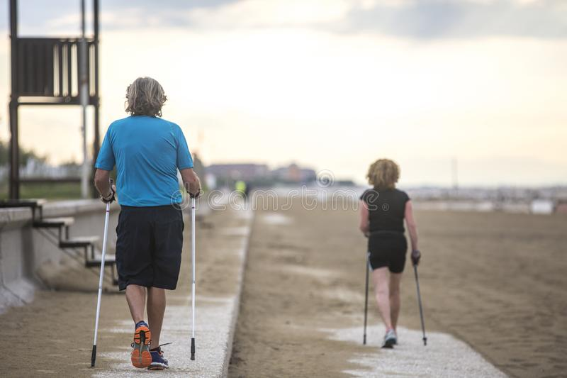 Älterer Paare Nordic, der auf den Strand geht lizenzfreie stockfotos