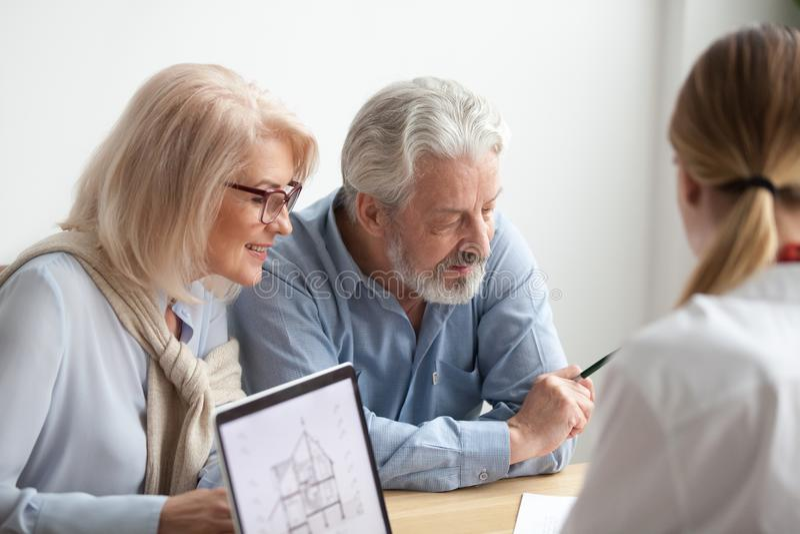 Älterer Paarlesevertrag bei der Sitzung mit Immobilienagentur lizenzfreie stockfotos