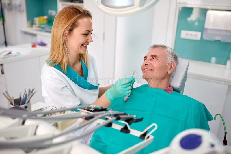 Älterer Patient im zahnmedizinischen Stuhl mit weiblichem Zahnarzt stockfotos