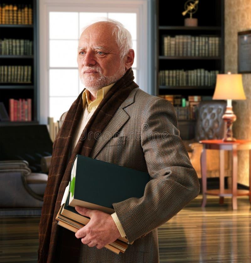 Älterer Professor mit Büchern am Bibliotheksraum lizenzfreie stockfotografie