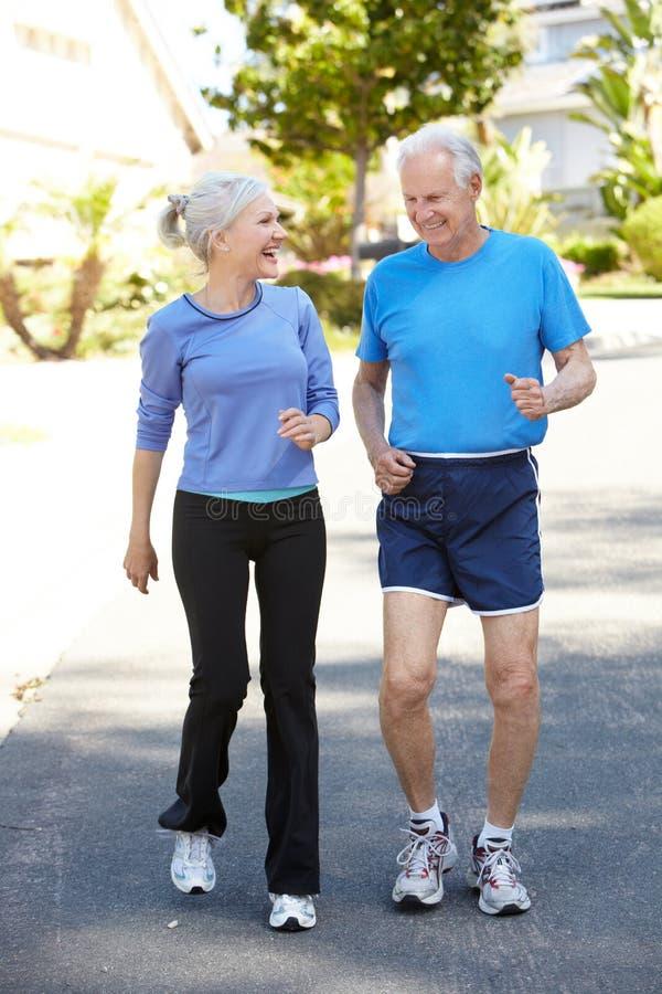Älterer rüttelnde Mann und jüngere Frau lizenzfreies stockfoto