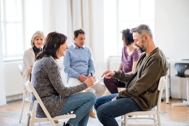 Älterer Ratgeber mit Klemmbrett sprechend mit einem Mann während der Gruppentherapie stockfoto