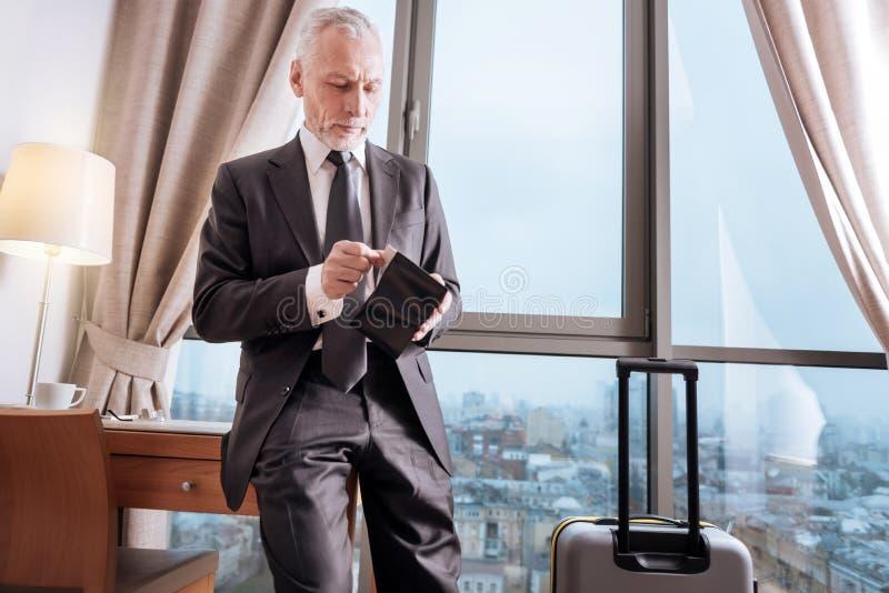 Älterer reflektierender Mann, der seine Geldbörse überprüft lizenzfreie stockfotografie