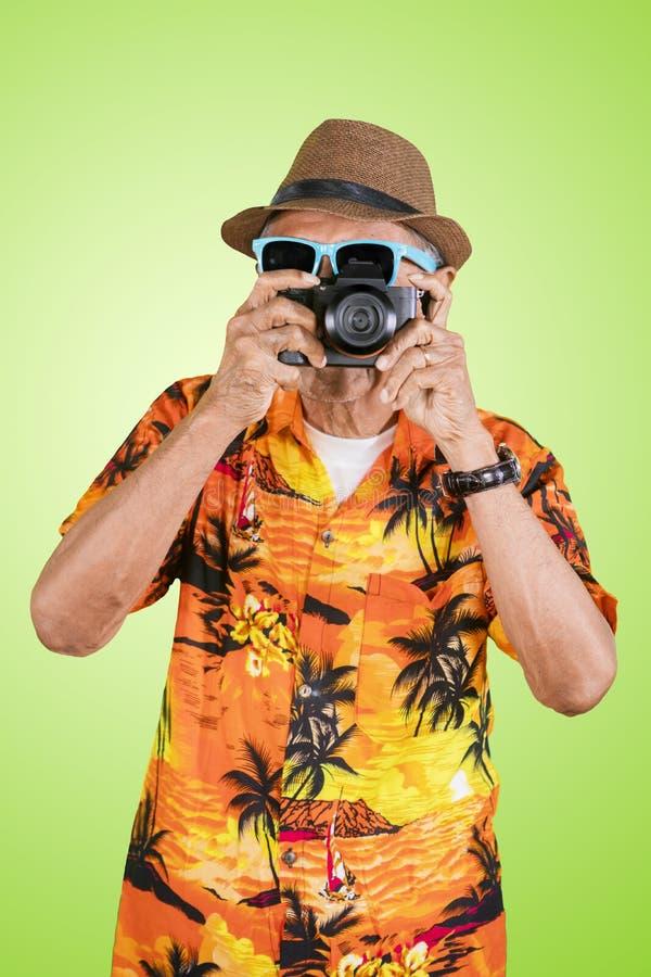 Älterer Reisender, der eine Digitalkamera im Studio verwendet stockbilder