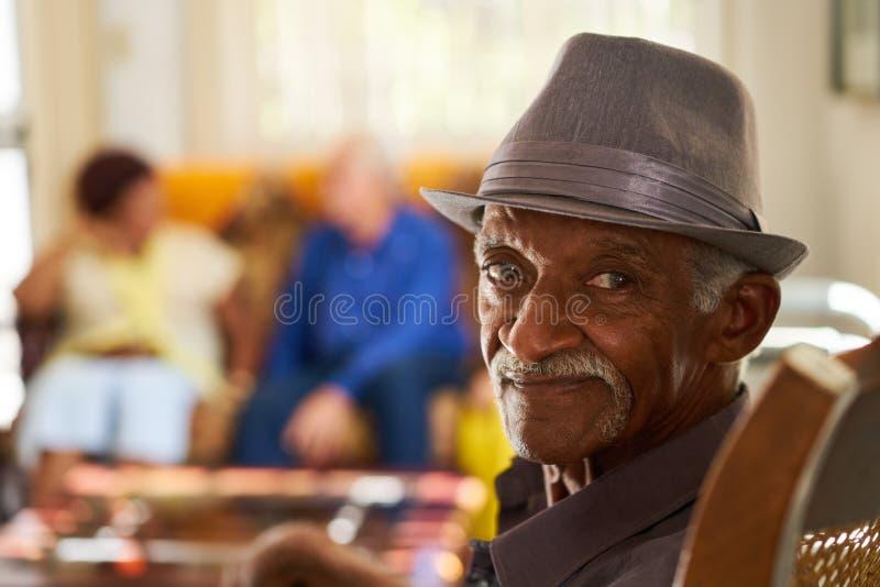 Älterer schwarzer Mann mit dem Hut, der Kamera im Pflegeheim betrachtet lizenzfreie stockbilder