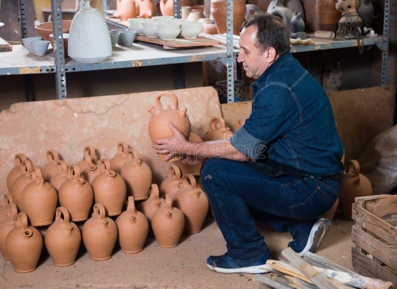 Älterer Töpfer an der keramischen Werkstatt lizenzfreie stockfotos