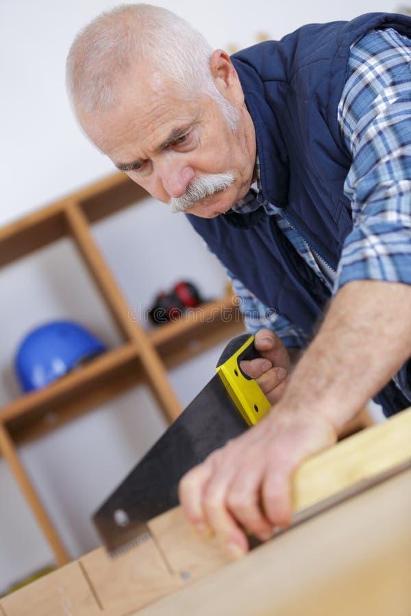 Älterer Tischler, der in der Werkstatt arbeitet stockfoto