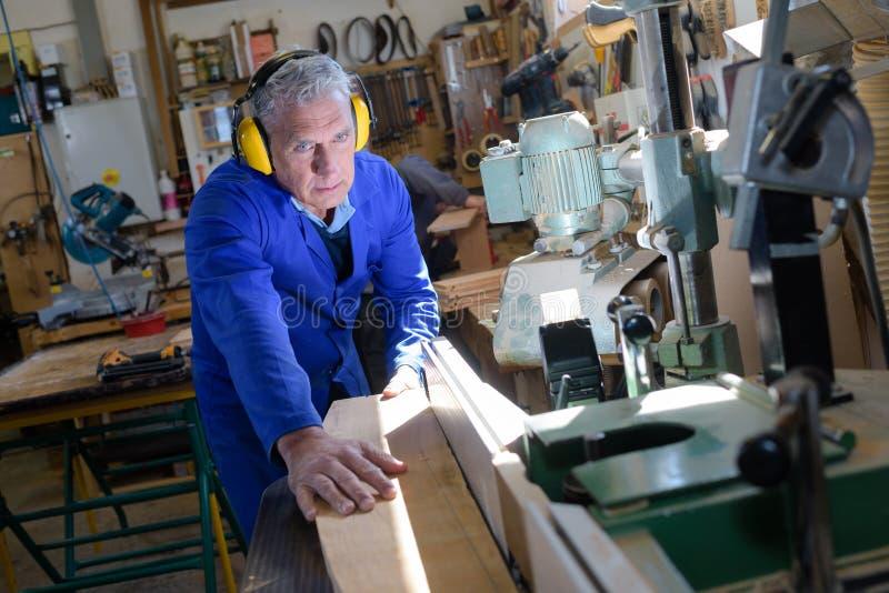 Älterer Tischler, der in der Werkstatt arbeitet lizenzfreie stockfotografie