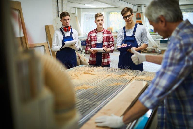 Älterer Tischler, der wie man mit Holz zeigt, arbeitet lizenzfreie stockfotografie