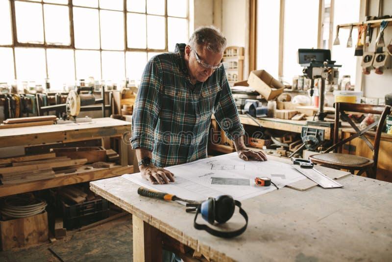 Älterer Tischler, der Zeichnung studiert stockbilder