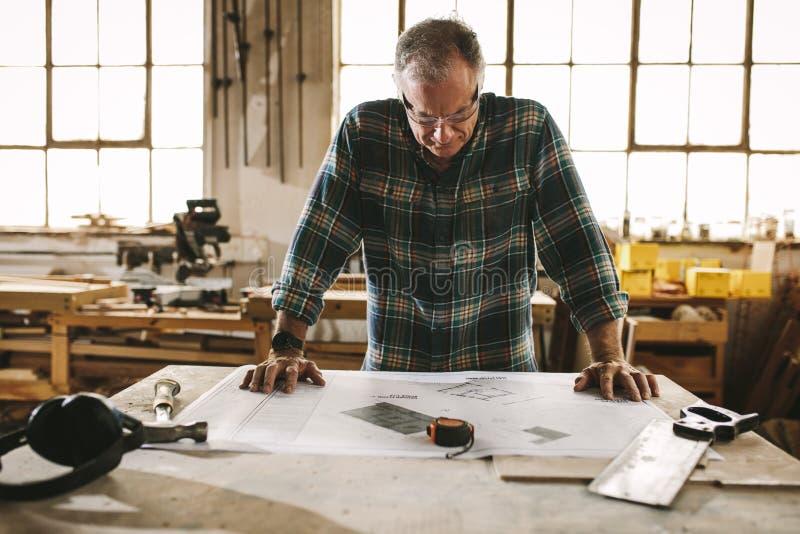 Älterer Tischler, der Zeichnung in der Werkstatt überprüft lizenzfreie stockfotos