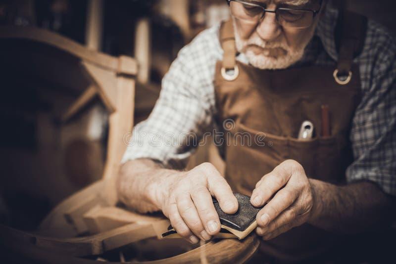 Älterer Tischler mit Glasporträt stockfoto