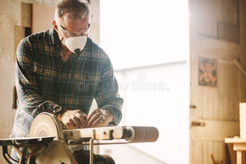 Älterer Tischler mit Maske unter Verwendung der Bandschleifmaschine stockbild