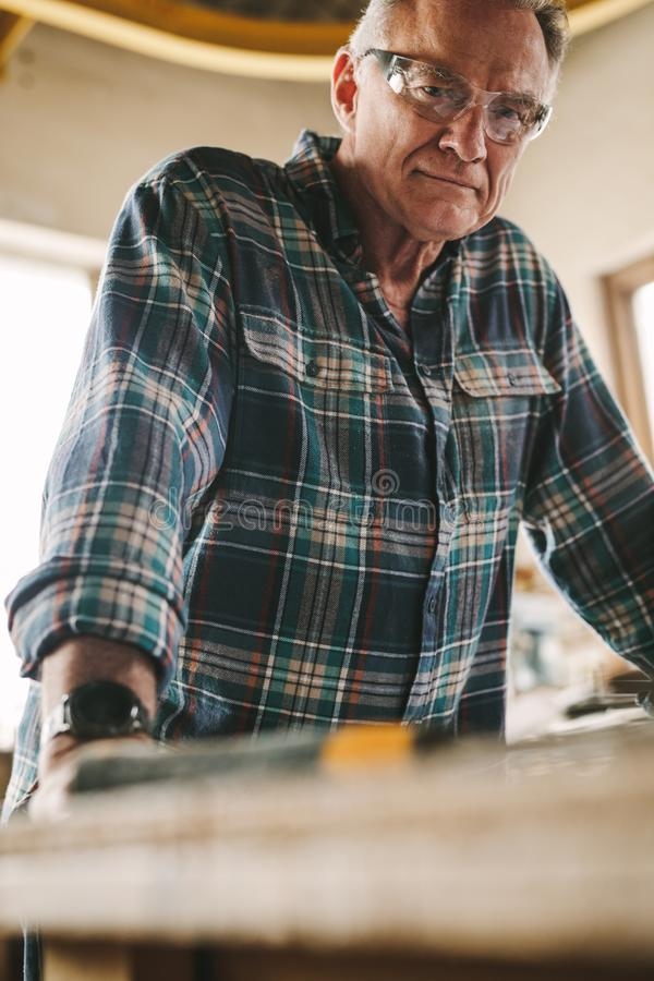 Älterer Tischler mit schützender Augenabnutzung stockbild