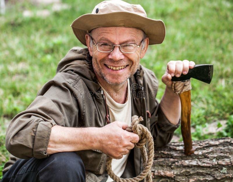 Älterer touristischer Mann mit Axt lizenzfreie stockbilder