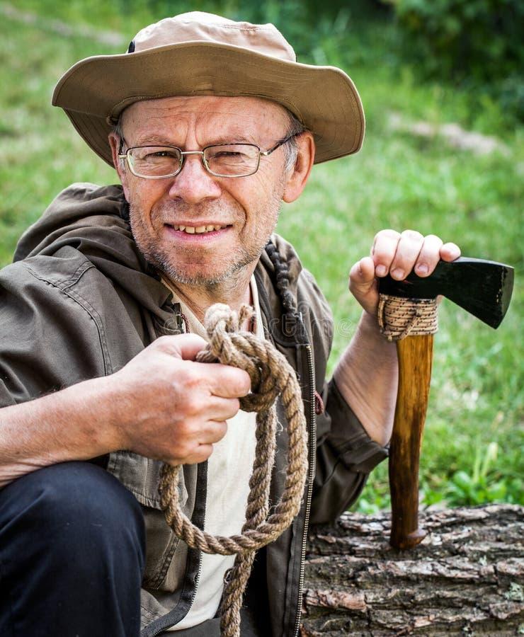 Älterer touristischer Mann mit Axt stockbilder