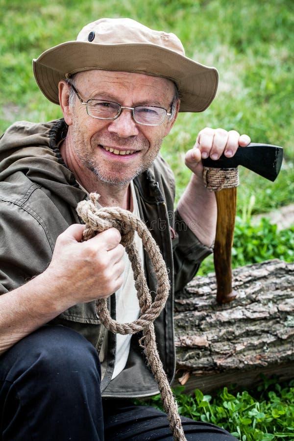 Älterer touristischer Mann mit Axt stockbild