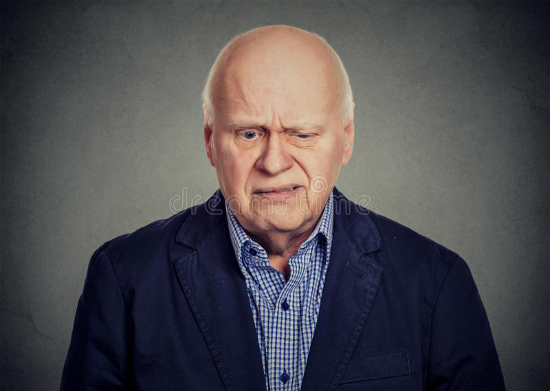 Älterer trauriger skeptischer Mann, der unten schaut stockbild