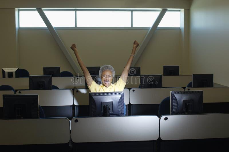 Älterer weiblicher Professor Celebrating Victory In Computer Classroom lizenzfreie stockbilder