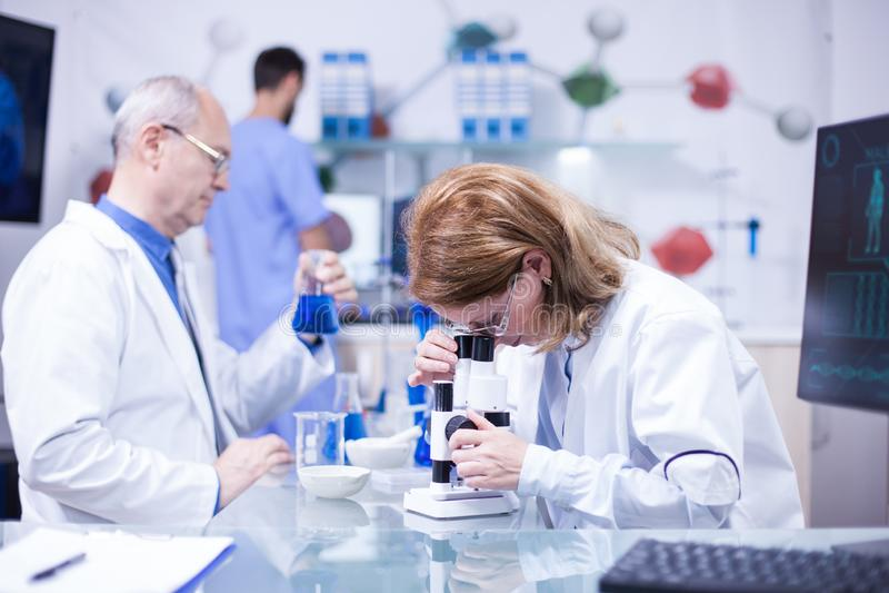 Älterer weiblicher Wissenschaftler, der in einem Labor gegen Krankheiten arbeitet lizenzfreie stockfotografie