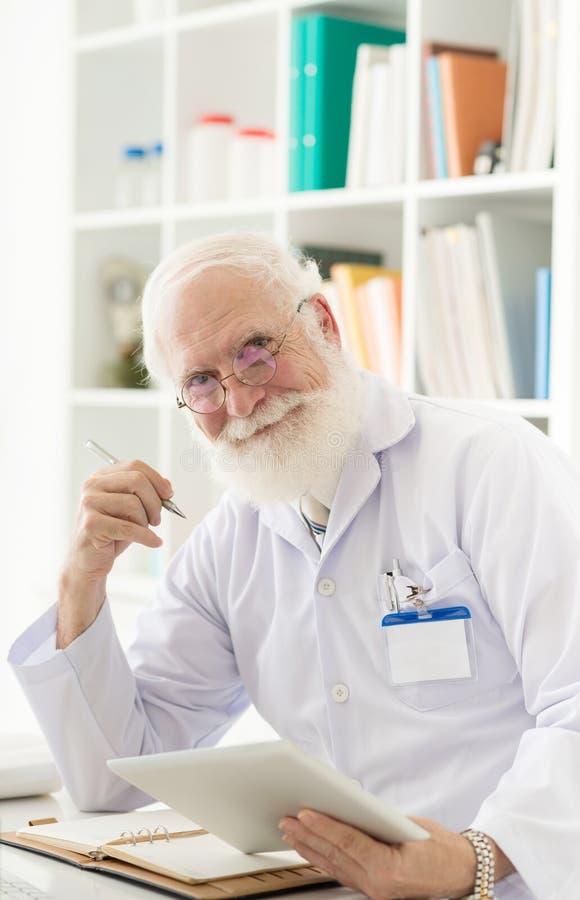 Älterer Wissenschaftler an seinem Arbeitsplatz stockfotos