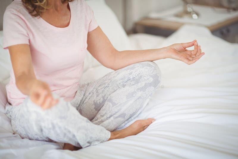 Älteres übendes Yoga auf Bett stockfotos