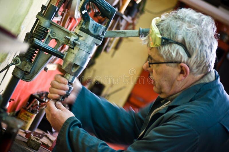 Älteres Arbeiterporträt mit Bohrgerät stockbilder