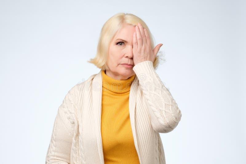Älteres Auge der Frauenbedeckung eine mit ihrer Hand stockbilder
