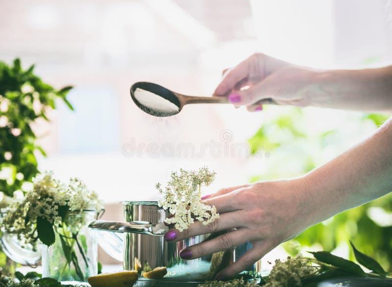 Älteres Blumensirupkochen Weibliche Handströmender Zucker vom Löffel im Topf mit Elderflowers auf Küchentisch stockbilder