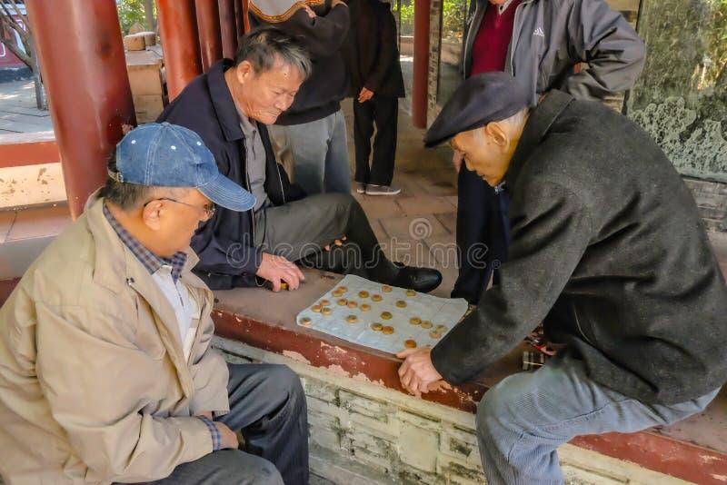 Älteres chinesisches Volk ließ sich entspannt und chinesisches Schach im ererbten Tempelpark spielend Foshan-Stadtporzellan stockfotos