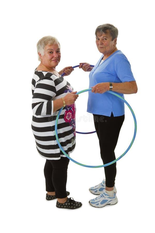 Älteres Damenhandeln gymnastisch mit hula Band lizenzfreie stockfotografie