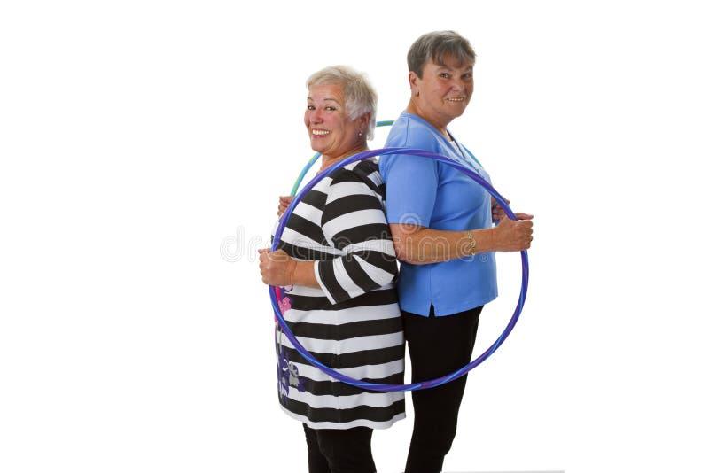 Älteres Damenhandeln gymnastisch mit hula Band stockbilder
