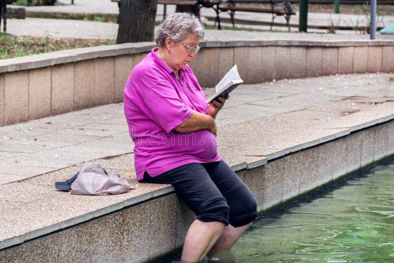 Älteres Damenlesebuch mit den Beinen im gesunden Wasser des heißen Badekurortes stockfoto