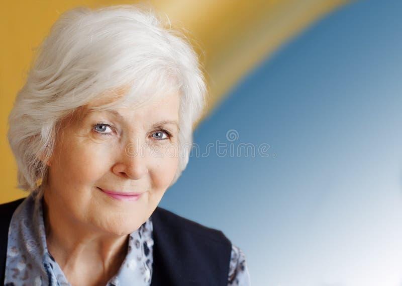 Älteres Dameportrait auf Blau lizenzfreie stockfotos