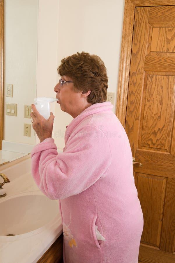 Älteres Frauen-Asthma-medizinischer Inhalator lizenzfreie stockfotos