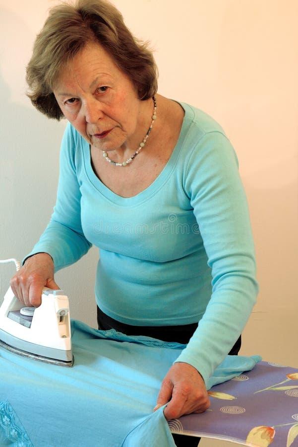Älteres Frauenbügeln lizenzfreie stockfotos