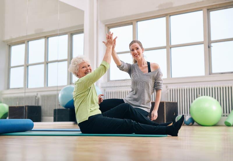Älteres Frauengeben ihrem persönlichen Trainer hoch--fünf lizenzfreie stockfotografie