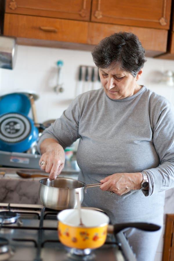 Älteres Frauenkochen stockfoto