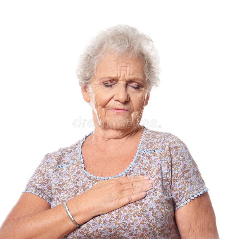 Älteres Frauenleiden vom Herzinfarkt gegen weißen Hintergrund lizenzfreie stockfotografie