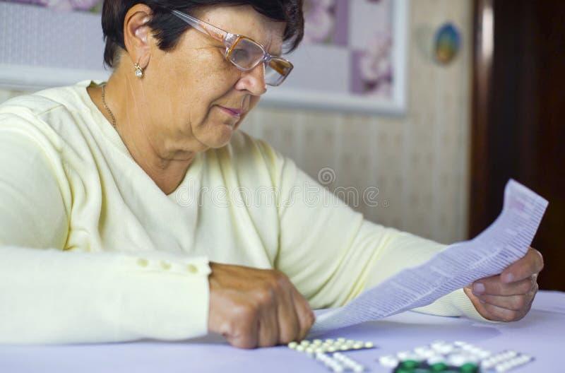 Älteres Frauenleseinformationsblatt der vorgeschriebenen Medizin bei Tisch sitzend zu Hause stockbilder