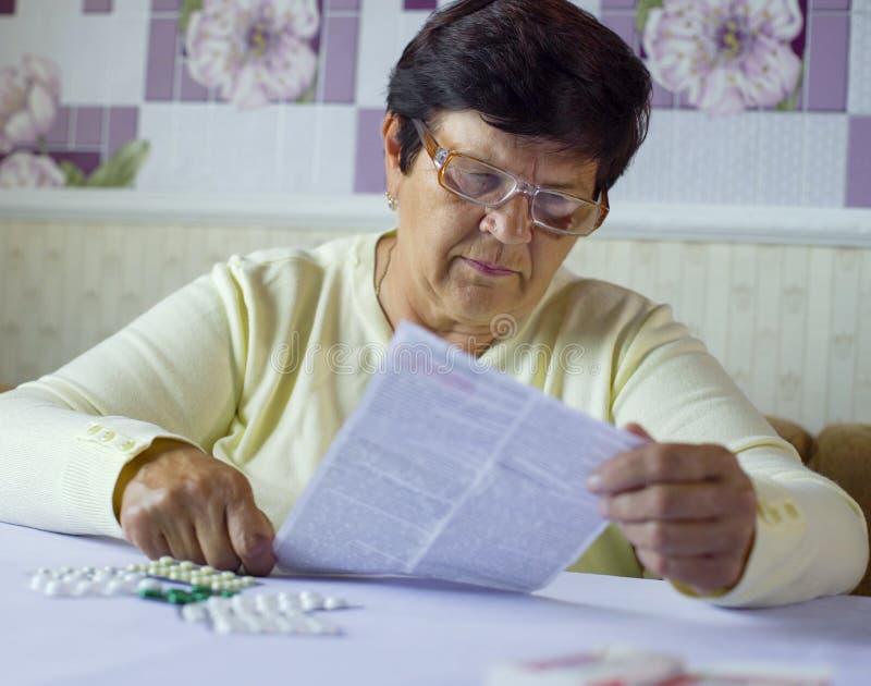 Älteres Frauenleseinformationsblatt der vorgeschriebenen Medizin bei Tisch sitzend zu Hause lizenzfreies stockfoto