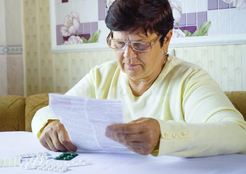Älteres Frauenleseinformationsblatt der vorgeschriebenen Medizin bei Tisch sitzend zu Hause stockbild